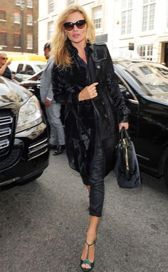 Supermodel Kate Moss, flaunting chic cat-eye shades, added a pop of color to her all-black ensemble with emerald-hued heels!