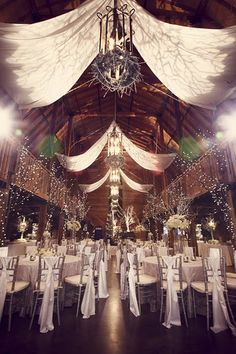 Ceiling drapes with gobo projections, trees with pealights, chiavari chairs with sash detail
