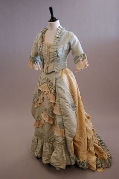 a fancy dress of turquoise faille and yellow damask, a tiered and frilled petticoat, 1880s.