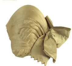 Bindmössa för kvinna, av ljusgrönt, nu bleknat siden försett med rynkband av linne och två rosetter av sidenband i samma färg som mössan. Mössan fodrad med handtryckt tyg i rött och gult. Stycke saknas.