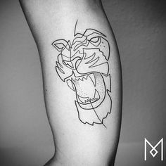 Continuous line style lion tattoo on the right inner arm.