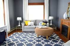 Den with wood trim and hardwood floors. Walls painted blue-grey, graphic blue rug and light grey furniture with pops of yellow too. Awesome.