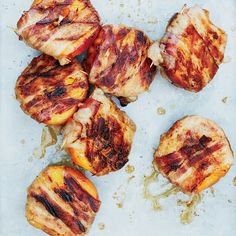 "Bacon-Wrapped Peaches- Brooklyn butcher Tom Mylan likes wrapping sweet, juicy peaches in bacon and grilling them until they're nicely charred. The secret ingredient, he says, are the grilled scallions tucked into the peach pit nook, ""for the win. 