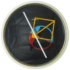 Geometric Wall Clock by George Nelson for Howard Miller A geometric wall clock by George Nelson for Howard Miller. The hands that keep the time on this atomic piece are a blue and red circle, a long white hand, and a yellow diamond. Encompassed in a round plastic face with an original Howard Miller emblem on the black background. Looks great with mid century decor, memphis style, or with the resurgence of the 80s look.