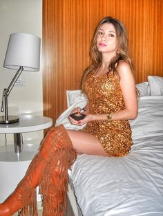 Amateur blonde on bed in gold sequined minidress and fringed OTK boots