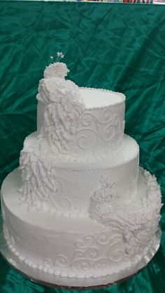 White peacock wedding cake. This version is a fondant neck and body covered in butter cream feathers.
