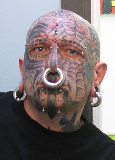 Full face tattoo, piercings, extreme body modification