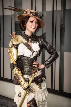 Mechanical Armed Steamgirl (costume consists of hat, goggles, leather bolero jacket, white blouse, underbust corset, mechanical arm with harness, belt with satchels, cane, ivory skirt) - For costume tutorials, clothing guide, fashion inspiration photo gallery, calendar of Steampunk events, & more, visit SteampunkFashionGuide.com