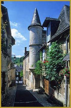 Photo au coeur de l'été de la rue Droite en fleurs, avec ses belles demeures Renaissance, dont cette belle maison à échauguette de deux étages, dans le centre historique de Turenne. Visiter Turenne, photos des plus beaux villages de France.
