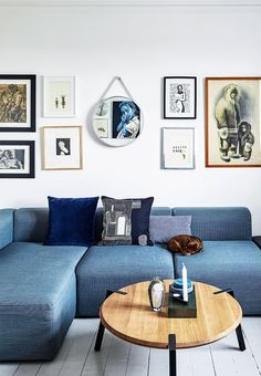 Living room with a blue sofa and wooden designer coffee table. Perfectly decorated with a gallery wall.