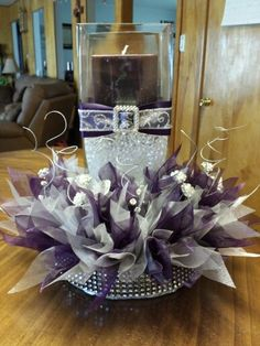 Wedding center peice with plum and silver organza ribbon, bling floral picks, and silver twisted floral decor.