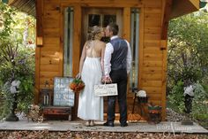 sneaking a kiss at The Little Log Wedding Chapel in Niagara. Rustic weddings and photography props