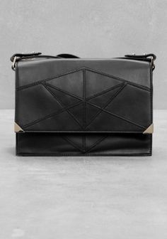 A chic leather shoulder bag crafted from smooth leather, featuring a graphic pattern comprised of seams.