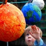 solar system balloons and paper mache painted to look like the sun and planets