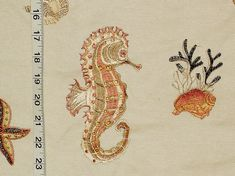 An embroidered copper seahorse fabric. This embroidered seahorse fabric has coral, star fish, and seashells. It is perfect for a beach cottage