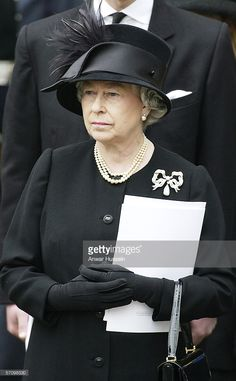 Queen Elizabeth II watches as the Queen Mother's coffin is driven from Westminster Abbey on April 9, 2002. The Queen Mother's coffin will be taken to St George's Chapel in Windsor, where she will be laid to rest next to her husband, King George VI.