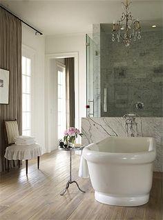 tub in front of shower, shower door on side- chandelier and slab of marble behind freestanding bathtub