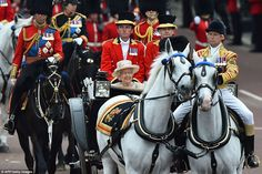 The Queen smiles as she heads back towards Buckingham Palace from Horse Guards Parade after taking part in Trooping the Colour
