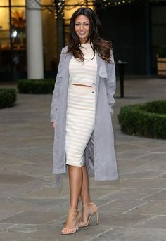 Michelle Keegan in a matching striped crop top and midi skirt and a gray trench