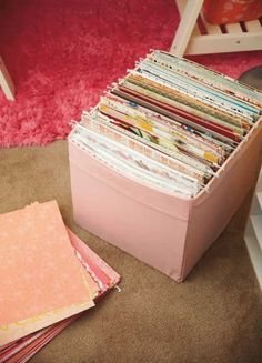 To keep paper easily accessible and affordable, use 12 x 12 hanging file folders and fabric storage bins. Each color (or theme, or pattern) is organized in its own folder. With this method, you can easily pull out and flip through any folder to find that perfect sheet.