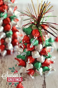 "In the holiday spirit for a festive centerpiece, but aren't super crafty? These ""Kiss""-mas Tree Centerpieces made with Hershey's Kisses are super easy to make and are a fun project to work on with kiddos!"