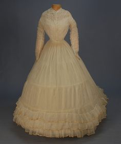 TRAINED GAUZE WEDDING GOWN with SHIRRED BODICE, 1860's. 2-piece white cotton, the bodice with vertical shirring front, back and on the long sleeves, sleeveless twill under-bodice with two bones, hooks & eyes. Unlined skirt with three hem ruffles edged in cream ribbon.