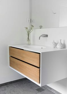 Bespoke bathroom furniture from Garde Hvalsoe in Oak wood. The cabinet and tabletop are made from Corian with an integrated Corian sink. This beautiful piece of furniture has the three corner stones of Scandinavian design: simplicity, minimalism and functionality. See more at www.bynordichands.ch