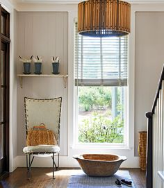 The owners of this retreat snagged the entryway's bread-kneading bowl at Atlanta's Scott Antique Market. The canvas-backed chair is Simply Home.   - CountryLiving.com