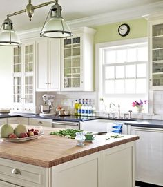 This kitchen sings with the perfect shade of green, Benjamin Moore's Chameleon.   - CountryLiving.com