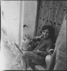 Niña de Madrid, con vestido de lunares sentada a la puerta de una casa junto a varios botijos.
