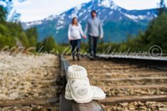 Alaska Maternity Photography. Mother and Father to be walk down railroad tracks with baby booties in foreground. Alaska mountain backdrop.