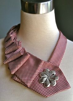 Tie necklace with brooch from Etsy.  Tutorial at http://www.maybematilda.com/2011/05/pleated-necktie-necklace.html