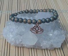 Matte blue green hematite bracelet with lotus charm.Size 6in wrist