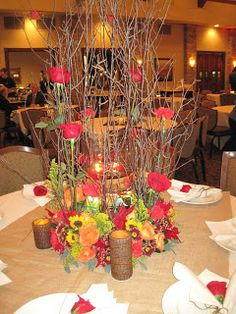 A ring of fresh flowers surrounds a large glass cylinder vase with red floating candles.  Tall twigs give height to the arrangement but do not totally cover the view from across the table.