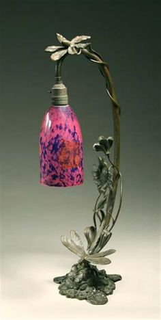 Art Nouveau Style Bronze and Glass Lamp The standard formed as a drooping flower stem ending in a mottled pink and blue glass shade cased in clear glass with foil inclusions, on a naturalistic base surmounted by a dragonfly.