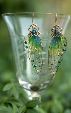 The Spriggan Fairy Wing earrings are made with our green and blue toned special ombre mini fairy wings and accented with Swarovski rhinestones and a filigree brass stamping. The ear wires are 18 kt gold plated These earrings are so stunning in person, we combined our love art