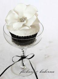 Black cupcake with white decorative flower.  #weddings #cake #desserts #black