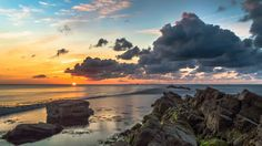 A tranquil scene, rocks in the foreground whilst the sea laps at the shore. Bright orange sun rises just behind the water in the horizon -phoyo by Andy Lyons