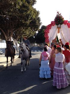 Andalusian horses passing an ox drawn cart with people dressed in traditional Andalusian dresses. Torremolinos City Festival 2015
