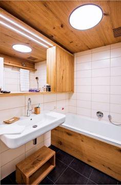 Z důvodu nenavyšování rozpočtu byly obklady předepsané developerem ponechány a doplněny dřevěným obkladem stropu i smaltované vany (Kaldewei) a dalšími dubovými skříňkami. Keramické umyvadlo značky Kolo je doplněno baterií Hansgrohe