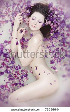 Attractive naked girl enjoys a bath with milk and rose petals. Spa treatments for skin rejuvenation by Kryvenok Anastasiia, via Shutterstock...