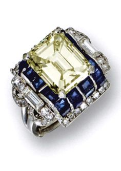 FANCY YELLOW DIAMOND AND SAPPHIRE RING, CIRCA 1935  Set with an emerald-cut fancy yellow diamond of 6.66 carats, framed by calibré-cut and round sapphires, further bordered by single-cut diamonds, the openwork, scalloped shoulders also enhanced with 2 baguettes, mounted in platinum.