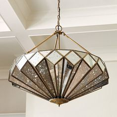 From beneath, the faceted mercury glass panels of our Rose Chandelier resemble the petals of an open rose. Every pane is angled to capture and reflect light to create a shimmering focal point. Rose Chandelier features:Striking over a desk or barHandmadeIron and copper frameAntique gold finishPierced finial
