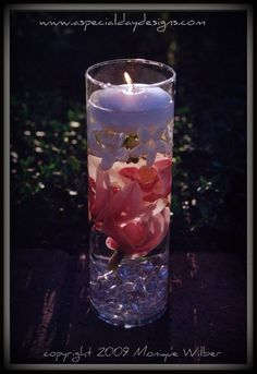 Floating candle with layers of clear gems and flowers below