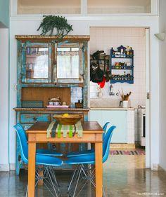 Sala de jantar tem cristaleira de madeira de demolição e cadeiras eames na cor azul.