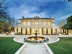 Elegant white mansion with blue tile roof, huge windows, balconies to die for and sprawling grounds