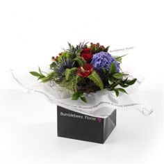 An expertly hand-tied bouquet of blue hydrangea, red roses, red anthurium, hypericum berries, blue thistle, shamrock, chrysanths, lime santini with seasonal foliage presented in exclusive Bumblebeez wrap and black gift bag.