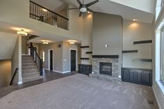 Stone fireplace with floating wood shelves and built-in cabinets. Balcony over great room. Vaulted ceiling.