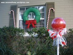 "Large hollow plastic balls (Michael's) or rubber play balls in red and green, wired ribbon, clear cellophane (the kind you wrap ""gift baskets"" with or use pre-formed ""gift basket"" plastic bags (Dollar Tree), PVC pipe (cut in equal lengths; I chose 3 ft. for my garden) to be used as the lollipop stands, large suction cups, strong adhesive, wired holiday ribbon, thin wire or pipe cleaners."