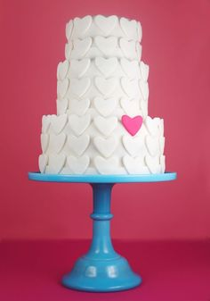 Pretty heart-covered tiered cake.  everything on this page for a heart and arrow wedding.  even shoes with hearts on the soles.  so cute